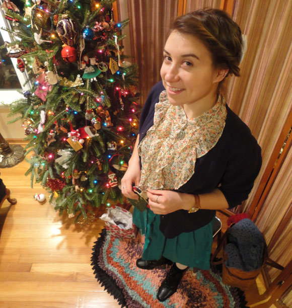 Julia sports a floral top, a navy cardigan, her green pocketed skirt, white tights, and black boots.