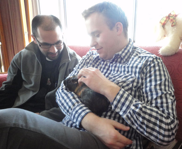 My brother Paul holds our guinea pig, Kiwi, as she receives a blessing from Father Simon.